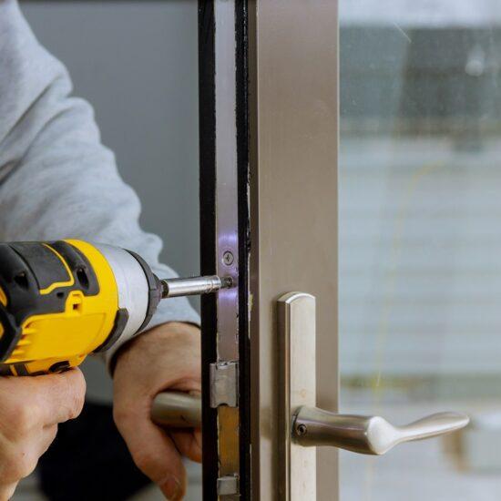 locksmith-in-installing-new-house-door-lock-hand-h-XVHVTG4